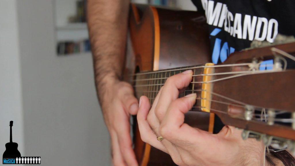 dedos pressionando cordas mão esquerda em formato de gancho